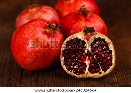 Whole and half-cutted grenadines on rustic wooden table - stock photo