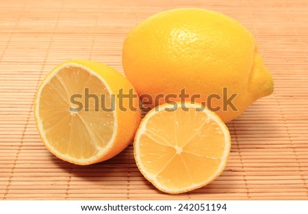 Whole and half of fresh lemons on wooden background, citrus, concept for healthy nutrition - stock photo