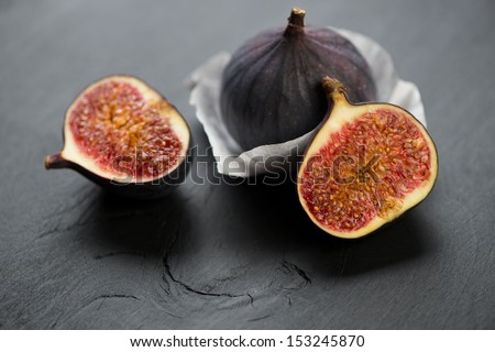 Whole and halved fig fruits on black wooden background