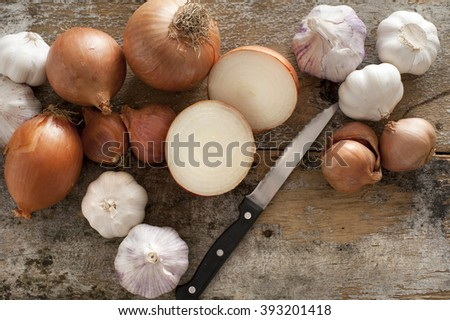 Whole and halved fresh uncooked garlic and onions of the Allium family with a knife on an old rustic kitchen table ready to prepare for cooking - stock photo
