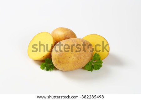whole and halved raw potatoes and parsley on white background