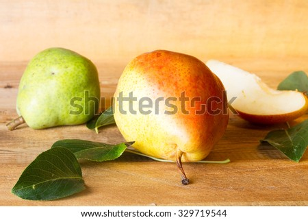 Whole and slice of ripe pears and green pear on a blackboard - stock photo