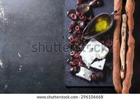 Whole and sliced black olives and block of feta cheese with olive oil and homemade grissini bread sticks on black slate over dark background. Top view - stock photo