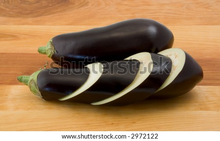 Whole and Sliced Eggplants on Wood Table - stock photo