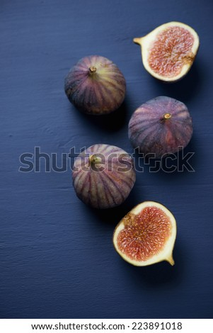 Whole and sliced figs on a dark blue wooden surface, above view - stock photo