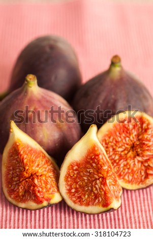 Whole and sliced figs on a pink fabric place mat. Focus on the sliced figs in the front of the image.