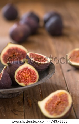 Whole and sliced figs on brown wooden garden table, sliced figs in an old metal plate