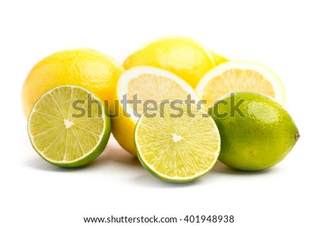 Whole and sliced fresh limes and lemons on over white background, DOF - stock photo