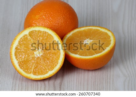 Whole and sliced fruits on table - cut in half orange pulp - diet, nutrition and natural vitamins concept