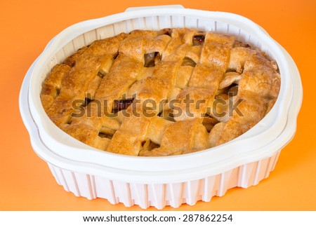 Whole apple pie in plastic tray:Home-baked cake with fruit or apple pie on a white plate isolated on an orange background - stock photo