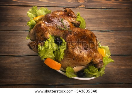 Whole baked chicken with garnish over wooden background. Holidays food. Rustic style. Toned image. Selective focus - stock photo
