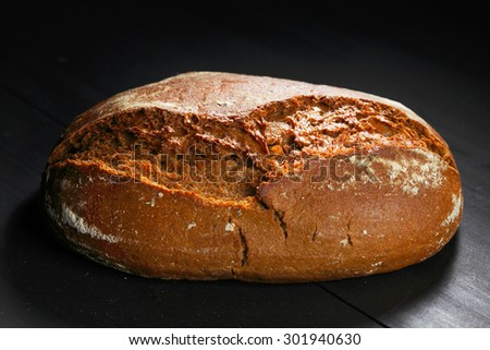 Whole black bread on wooden table close-up - stock photo