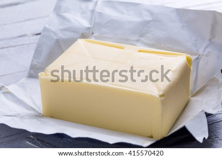 whole block butter in open packaging on white wooden background, front view - stock photo