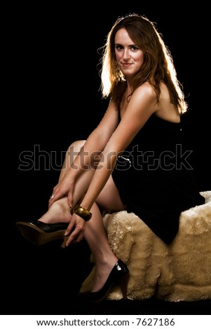 Whole body of an attractive young brunette woman in black dress  sitting on a fur covered stool over black