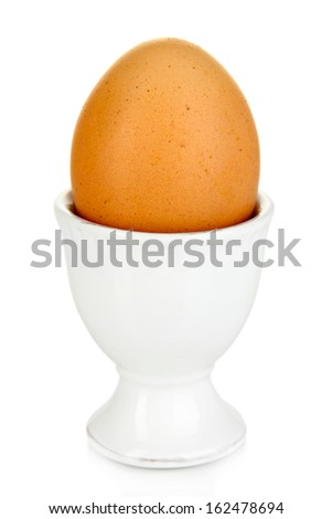 Whole boiled egg in egg cup isolated on white