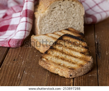 Whole bread and toasted slices of bread on a wooden background. - stock photo
