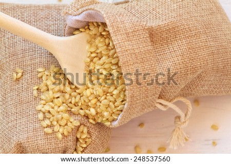 Whole brown rice on a vintage wooden background