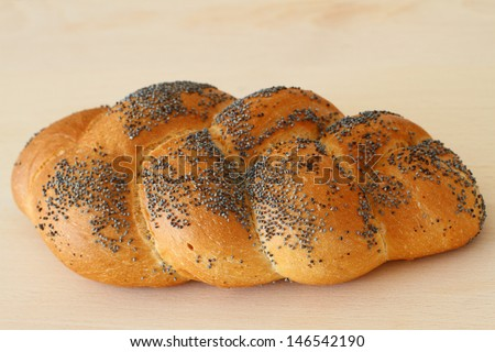Whole challah bread on wooden board, close up  - stock photo