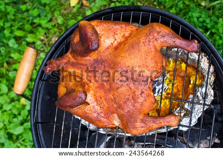 Whole chicken roasting on the BBQ - stock photo