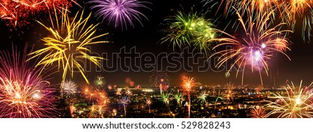 Whole city celebrating the New Year or a national event with lively fireworks, copyspace on the night sky