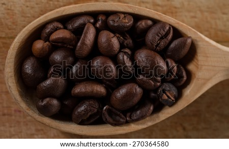 whole coffee beans in spoon on wooden background