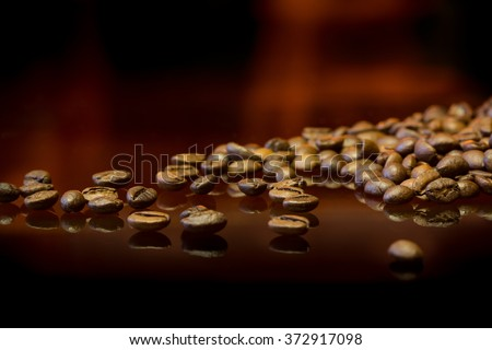whole coffee beans on a black mirrored background with reflection of fire