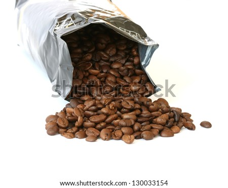 Whole coffee beans scattered on white background with silver packaging - stock photo