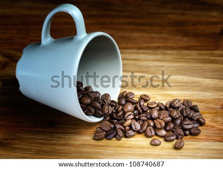 whole coffee beans spilled on wooden table with cup