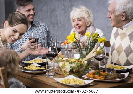 Whole family gathered at the dinner table, laughing and enjoying their time