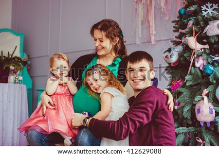 Whole family together next to the Christmas tree - stock photo