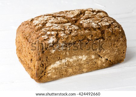 Whole farmers bread on white wooden background. - stock photo