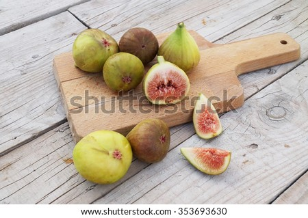 Whole figs and one fig sliced in half on top of a teak garden table.  - stock photo
