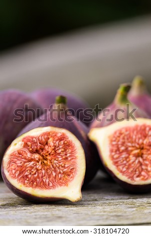 Whole figs on top of a teak garden table. Focus is on the front fig.