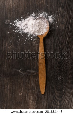 Whole flour in wooden spoon on dark vintage background. Tabletop view. - stock photo