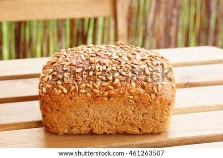 Whole fresh bread covered with seeds on wooden table