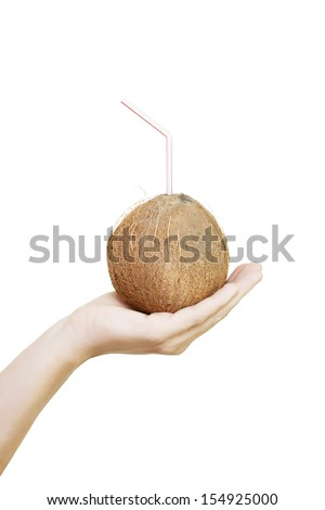 Whole fresh coconut husk with straw protruding from the top, conceptual of a delicious refreshing alcoholic tropical holiday cocktail - stock photo