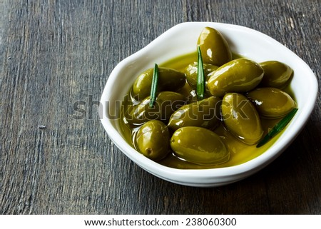 whole fresh green olives in a bowl of olive oil on a rustic wooden tabletop, selective focus  - stock photo