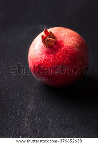 Whole fresh juicy pomegranate with water droplets on a dark background, selective focus