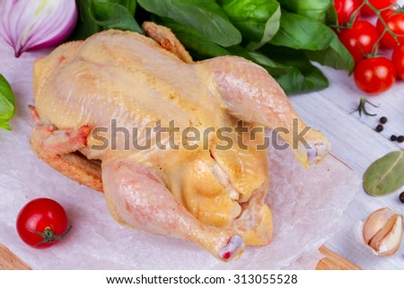Whole fresh raw chicken prepared for roast with thyme, basil, garlic and tomatoes cherry - stock photo