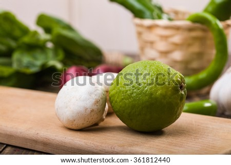 Whole fresh ripe lime with two raw crude white mushrooms on cutting board on table with potherbs, horizontal photo - stock photo