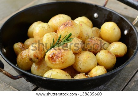 Whole fried young potato with spices and rosemary in old wok on wooden background - stock photo