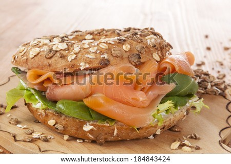 Whole grain bagel with smoked salmon on wooden background. Culinary healthy bagel eating. - stock photo