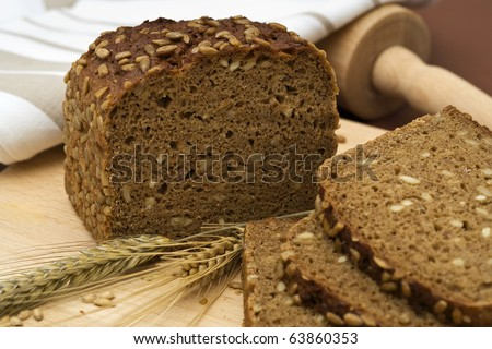 whole grain bread and slices with wheat and barley, rolling pin, towel - stock photo