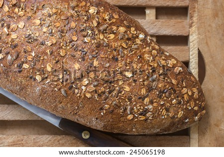 Whole Grain Bread and Vintage Knife on Wooden Cutting Board  detail - stock photo