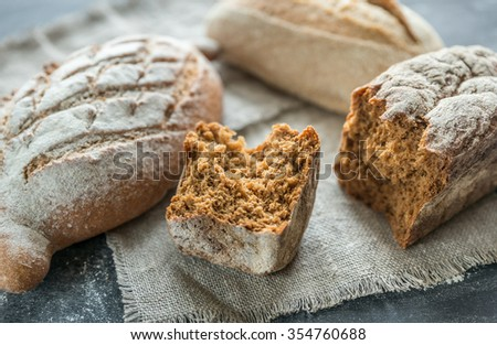 Whole grain breads on the dark wooden background - stock photo