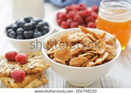 Whole-grain flakes in bowl with fresh berries on light background - stock photo