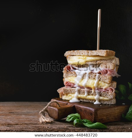 Whole grain grilled sandwich bread with melting hot cheese, ham, basil and pouring white sauce on wooden chopping board over dark background. With copy space. Square image