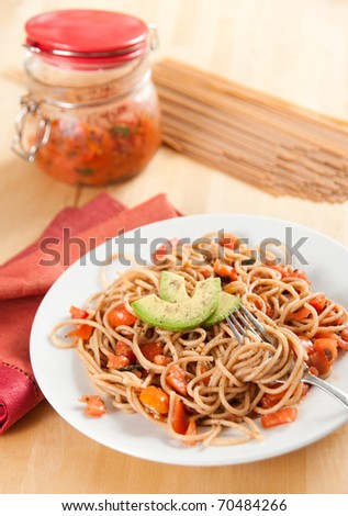 Whole Grain Pasta Spaghetti with Freshly Made Sauce and Avocado Slices - stock photo