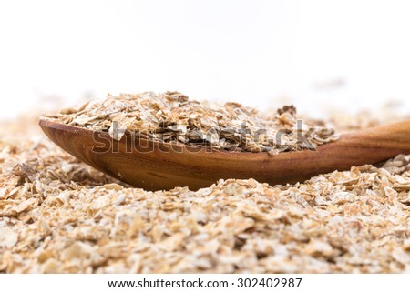 Whole grain, rolled oats flakes with wooden spoon