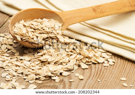 Whole grain, rolled oats with wooden spoon and homespun napkin. - stock photo